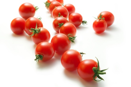 Fresh cherry tomatoes scattered isolated on a white background