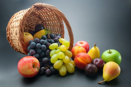 Fruits. Various fresh ripe fruits, scattered from wicker basket on dark gradient background
