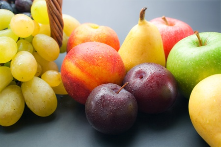 Fruits. Various fresh ripe fruits close-up: plums, peaches, pears, apples and grapes.