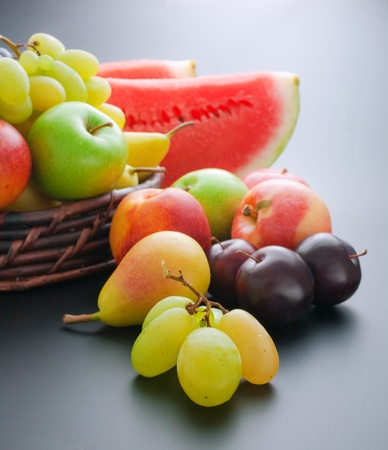 Various fresh ripe fruits placed in a wicker basket and around on gray gradient background