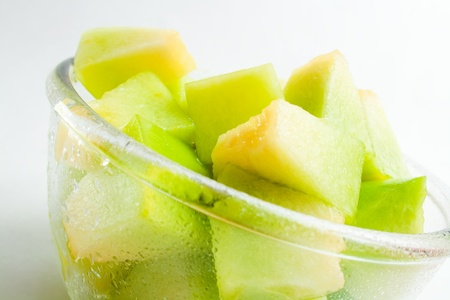 Fresh ripe melon honeydew pieces in a glass bowl  Stock Photo