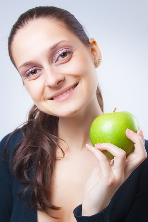 Beautiful young woman with a charming smile holds in his hand fresh ripe green apple