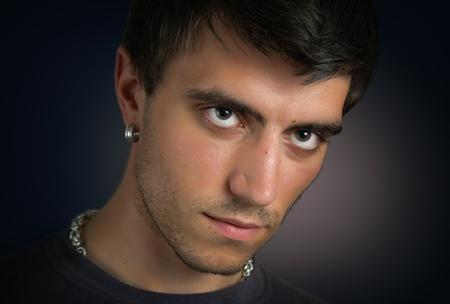 Portrait of beautiful and attractive young man with penetrating eyes and a silver earring in closeup on dark background photo