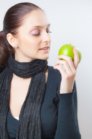 Beautiful elegant young lady with a charming smile and soft relaxing expression looking at fresh ripe green apple  in her hand Stock Photo - 8974781