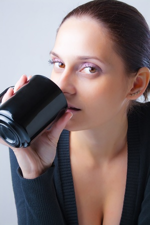 Beautiful young woman with staring eyes focused directly drink from black ceramic mug. Close-up isolated on neutral background.