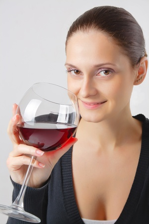 Beautiful young lady with a charming smile with a glass of red wine close-up isolated on a neutral background photo