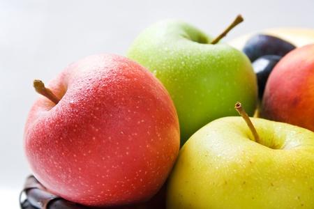 durazno: Manzanas. Varias manzanas frescas de maduras en primer plano de diferentes colores dispuestos en una cesta de mimbre aislada en fondo neuronal
