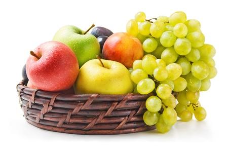 canasta de frutas: Frutos. Diversas frutas maduras dispuestos en una cesta de mimbre aislada sobre fondo blanco