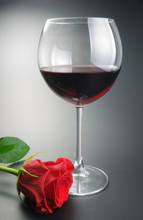 Glass of red wine and red rose flower arranged on neutral gradient background. photo