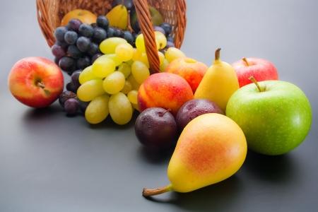 様々 な新鮮な熟した果実のクローズ アップ: 梅、桃、梨、リンゴ、ブドウは中立のグラデーション背景に枝編み細工品バスケットから散乱