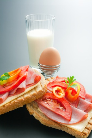 Breakfast. Fresh pork tenderloin sandwiches with cheese, tomato and pepper arranged in the company of soft-boiled egg placed in a special metal stand and glass of milk on neutral gradient background
