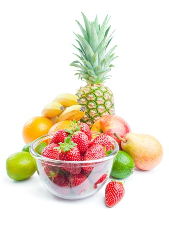 Fruits. Arrangement of vaus fresh ripe fruits: pineapple, bananas, oranges, pear, apple, limes and strawberries in a glass bowl isolated on white background Stock Photo - 9636099