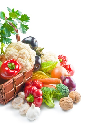 Mix of fresh ripe vegetables arranged in a wicker basket and around isolated on white background Stock Photo - 9720513