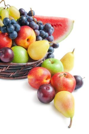Fruits. Various fresh ripe fruits placed in a wicker basket and around on white background.