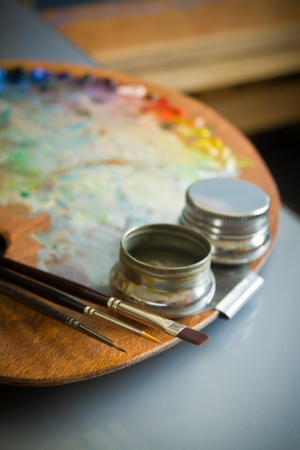 medium close up: Wooden artist s oil color palette with three artists paint brushes and metal twin dippers close-up on background of  art studio interior