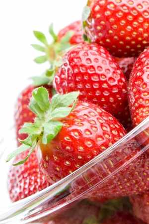 Strawberries. Fresh ripe strawberries in a glass bowl close-up isolated on white background.