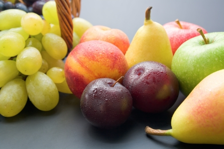 Fruits. Mix of fresh ripe fruits close-up: plums, peaches, pears, apples and grapes on neutral background.