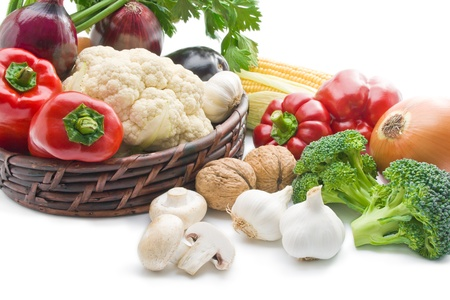 Vegetables. Mix of fresh ripe vegetables arranged in a wicker basket and around close-up  isolated on white background
