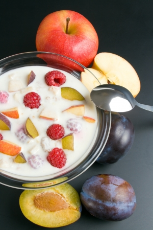 Yogurt with fruits. Glass bowl filled with yogurt mixed with fruit pieces arranged with spoon and some fruits around close-up  isolated on black background.
