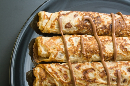Pancakes. Freshly baked rolled pancakes with chocolate in a black ceramic plate close-up. Stock Photo