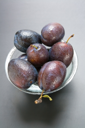 Plums. Fresh ripe plums in a glass bowl on a neutral gradient background. Stock Photo