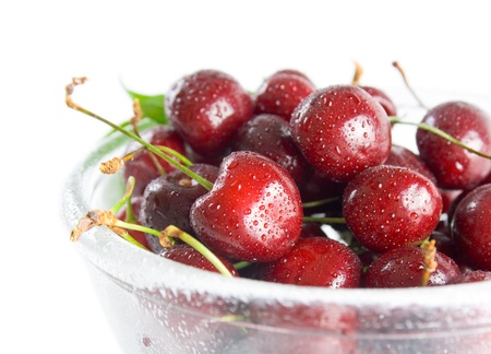 Cherries. Fresh ripe cherries in a class bowl close-up isolated on white background.