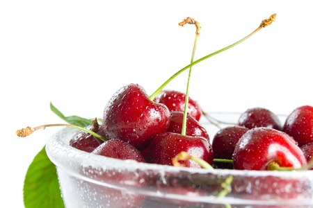 Cherries. Fresh ripe cherries in a class bowl close-up isolated on white background. Stock Photo