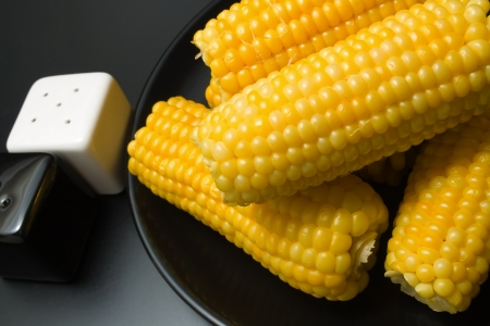 Corn cobs. Freshly cooked corn cobs close-up arranged in a black ceramic plate with salt and pepper shakers on dark background Stock Photo