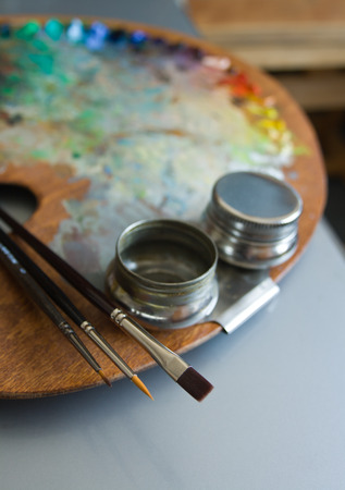 Wooden artist palette with three artists paintbrushes and steel twin dippers close-up on art studio interior background. Stock Photo