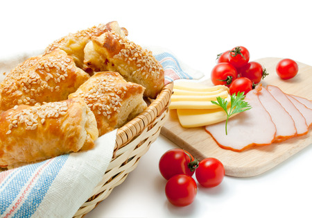 Freshly baked puff pastry patties sprinkled with sesame seeds in a wicker basket closeup arranged with cherry tomatoes cheese ham and parsley isolated on white background.