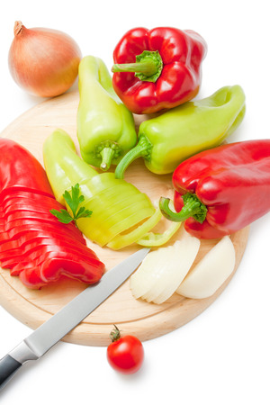 Fresh ripe red and green peppers and onions placed on a wooden cutting board and around arranged with kitchen knife cherry tomato and parsley sprig isolated on white background.