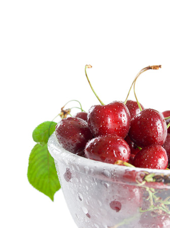 Fresh ripe cherries in a class bowl close-up isolated on white background