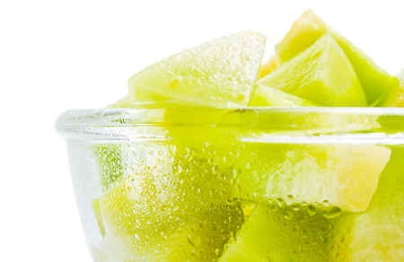 Melon honeydew portion. Rape fresh melon honeydew pieces in a glass  bowl close up  isolated on white background