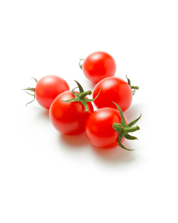 scattered on white background: Cherry tomatoes. Fresh ripe cherry tomatoes scattered isolated on a white background Stock Photo