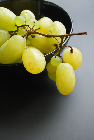 Grapes. Fresh ripe bunch of grapes placed in black ceramic bowl close up on neutral gradient background