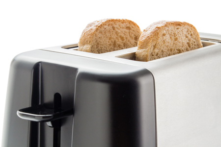 Toaster with bread slices. Electric toaster with two wholemeal bread slices close up isolated on white background.