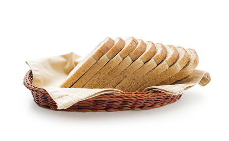 Wholemeal toast bread slices placed over cotton cloth in a wicker basket isolated on white background
