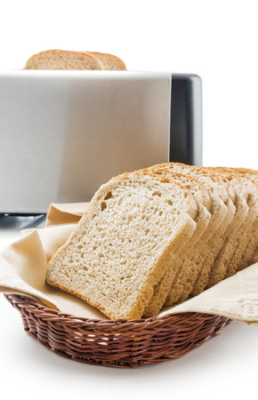 Wholemeal toast bread slices placed on a cotton cloth napkin in a wicker basket close up arranged with electric toaster isolated on white background.