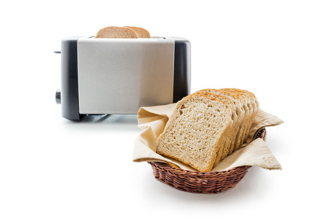Toast bread and toaster. Wholemeal toast bread slices placed on a cotton cloth napkin in a wicker basket close up arranged with electric toaster isolated on white background. Stock Photo