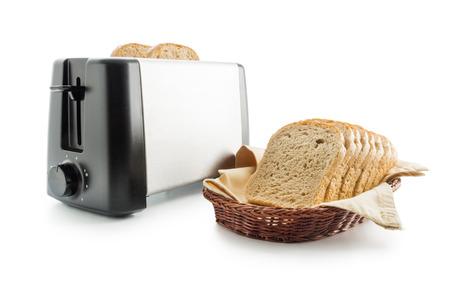 tela algodon: Rebanadas de pan tostadas integrales colocados sobre una servilleta de tela de algodón en una cesta de mimbre close up dispuesto con tostadora eléctrica aislada en el fondo blanco.