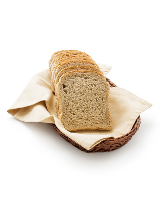 Toast bread in a basket. Wholemeal toast bread slices placed on a cotton cloth napkin in a wicker basket close up isolated on white background.