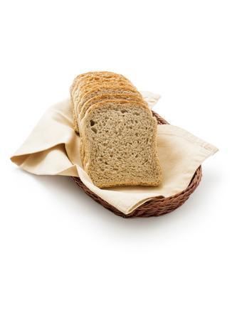 tela algodon: tostar el pan en una cesta. Rebanadas de pan tostadas integrales colocados sobre una servilleta de tela de algodón en una cesta de mimbre cerca aisladas sobre fondo blanco.