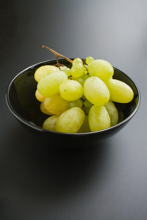 Grapes. Bunch of fresh ripe juicy grapes placed in black ceramic bowl on neutral gradient background
