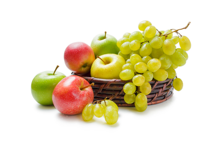 Various fresh ripe apples and grapes placed in a wicker basket and around isolated on a white background