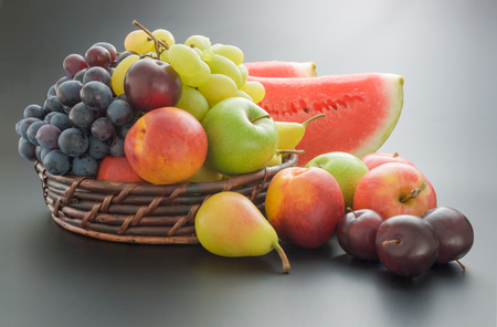 Fruits mix arrangement. Various fresh ripe fruits arranged in a wicker basket and around on neutral gray gradient background