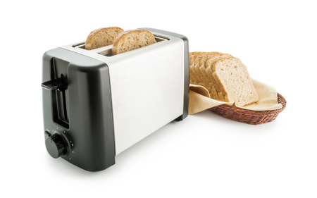 Toaster with bread slices. Electric toaster arranged with wholemeal toast bread slices placed on a cotton cloth napkin in a wicker basket isolated on white background. Stock Photo