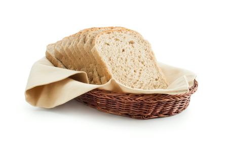 Rebanadas de pan tostadas integrales colocados sobre una servilleta de tela de algodón en una cesta de mimbre cerca aisladas sobre fondo blanco. Foto de archivo