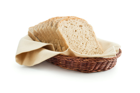Wholemeal toast bread slices placed on a cotton cloth napkin in a wicker basket close up isolated on white background.