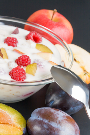 Yogurt with fruits. Glass bowl filled with yogurt mixed various with fruit pieces arranged with spoon plums and apples around close up  on dark  background