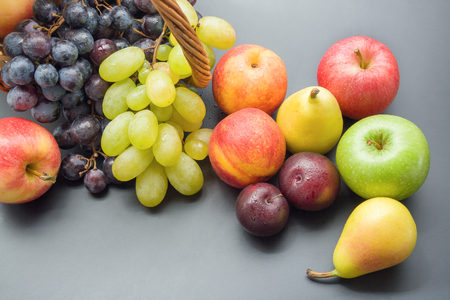 Bunch of fruits. Mix of various fresh ripe fruits top view plums, peaches, pears, apples and grapes on gray neutral background Stock Photo